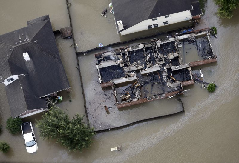 A burned out home is surrounded by floodwaters from Tropical Storm Harvey