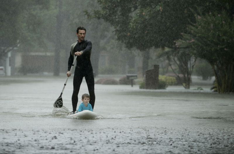 Alexendre Jorge evacuates Ethan Colman, 4, from a neighborhood inundated by floodwaters from Tropical Storm Harvey