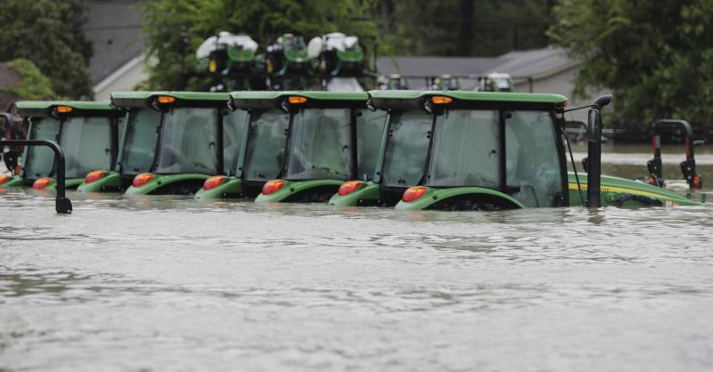 A row of tractors are surrounded by floodwaters from Tropical Storm Harvey