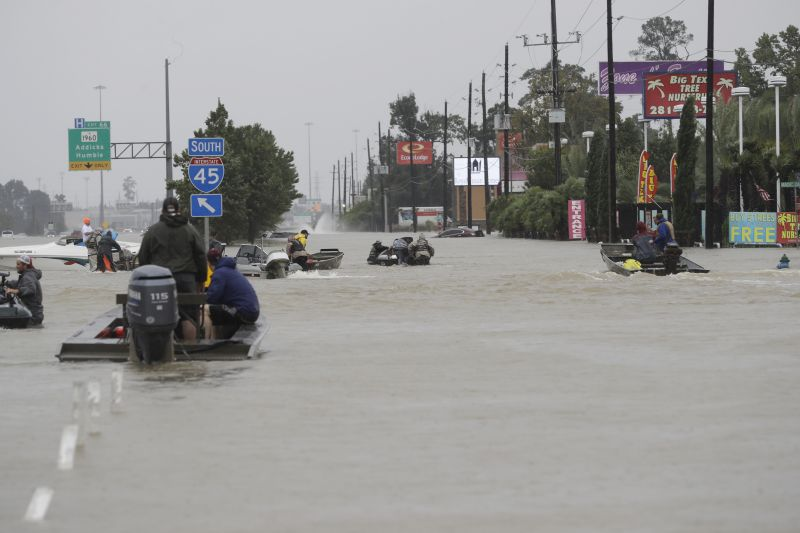 Volunteer rescue boats make their way into a flooded subdivision to rescue stranded residents