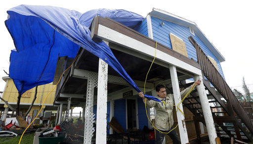 Man trying to tarp his home against further damage