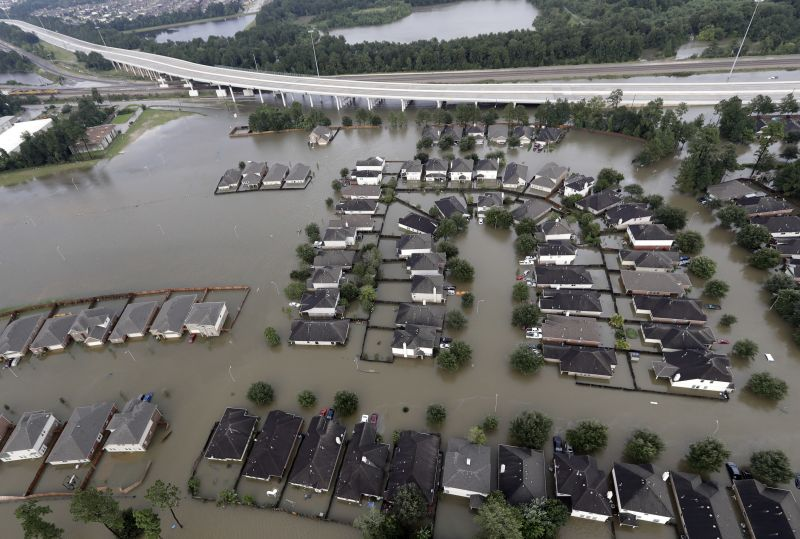 Homes are surrounded by floodwaters from Tropical Storm Harvey Tuesday, Aug. 29, 2017, in Spring, Texas