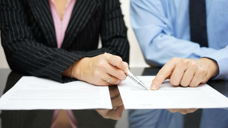 Business woman and man reading insurance policy
