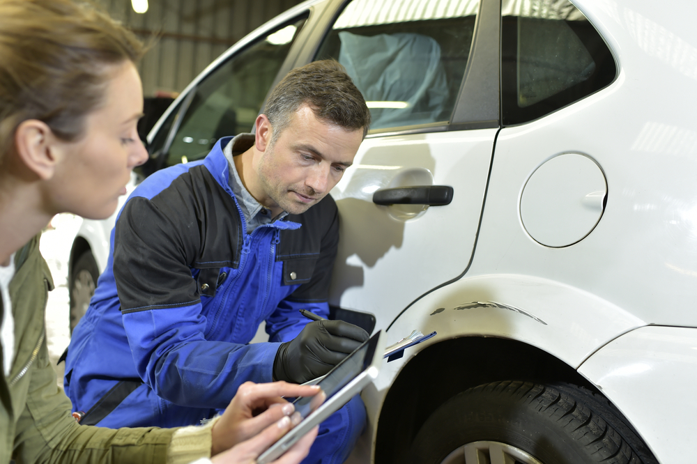 Insurance adjusters examining an auto claim
