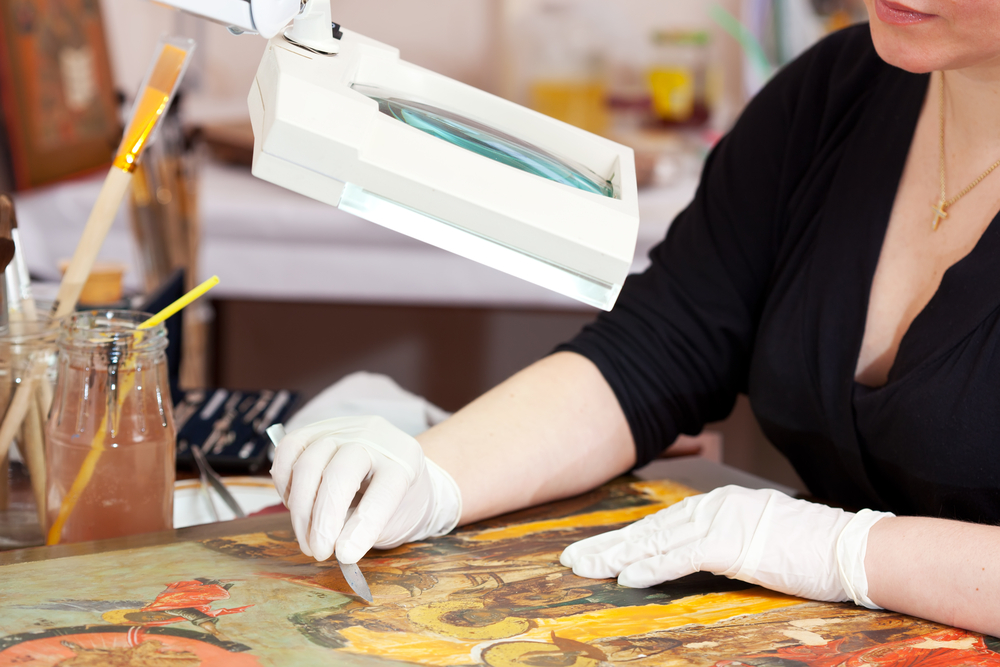art restorer working on a painting