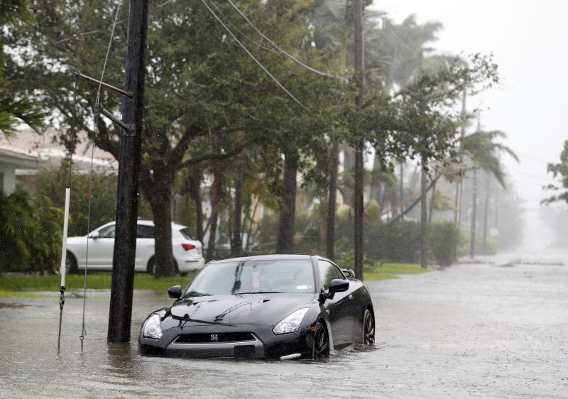 A car is parked on a flooded road as Hurricane Irma passes