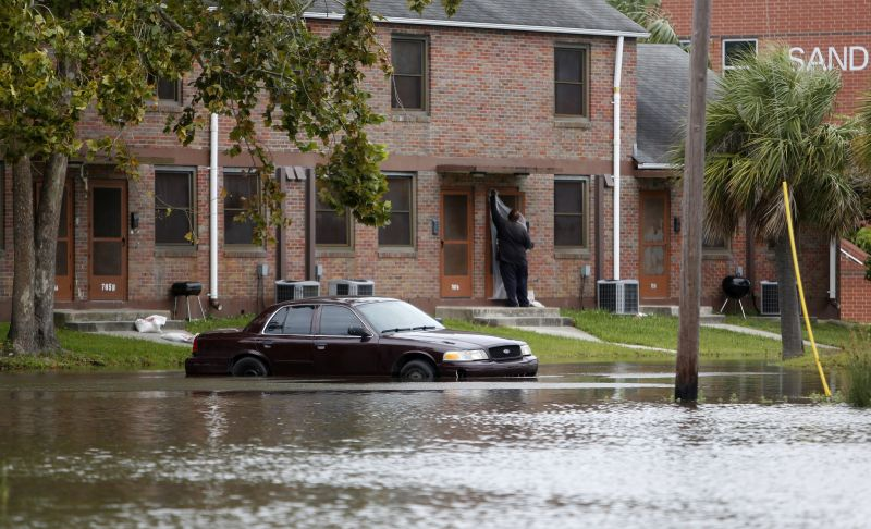 A Charleston, S.C. resident puts plastic up over his apartment door as a car rests in floodwaters