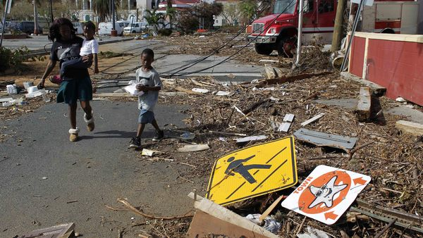 A woman with her two children walk past debris left by Hurricane Irma. (Photo: Associated Press/Ricardo Arduengo)