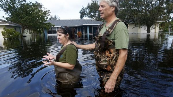 Kelly McClenthen walks through floodwaters with her boyfriend Daniel Harrison, after checking on her flooded home, in the aftermath of Hurricane Irma, which passed through yesterday, in Bonita Springs, Fla., Monday, Sept. 11, 2017. (AP Photo/Gerald Herbert)