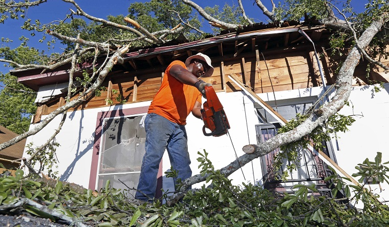 Removing a tree from a damaged structure is part of the repair of that structure and is separate from debris removal. Here, Pastor Michael Williams cuts branches from a wind blown tree on Monday, May 1, 2017, that fell on a family members home in Durant, Miss. Williams and members of his church helped remove tree debris from the structure. (AP Photo/Rogelio V. Solis)