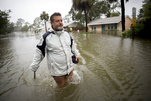 Tybee Island resident Joey Spalding walks in floodwaters by his house