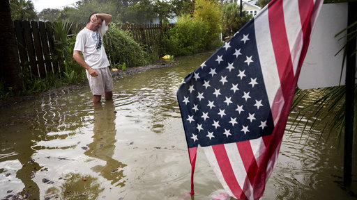 Joe Murphy stands in two feet of water in front of his house