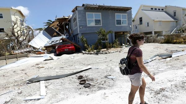Florida Keys resident Mae Skiver walks past homes damaged by Hurricane Irma in the neighborhood where she rode out the storm, Wednesday, Sept. 13, 2017, in Summerland Key in the Florida Keys. (AP Photo/Wilfredo Lee)