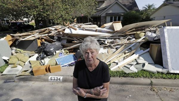 In this Monday, Sept. 11, 2017, photo, Arlene Estle stands outside her home which was damaged by floodwaters from Hurricane Harvey, in Houston. Victims of Harvey, desperate to rebuild their homes and lives, are facing the harsh reality that it may take months for an overwhelmed construction industry to address their needs. (AP Photo/David J. Phillip)