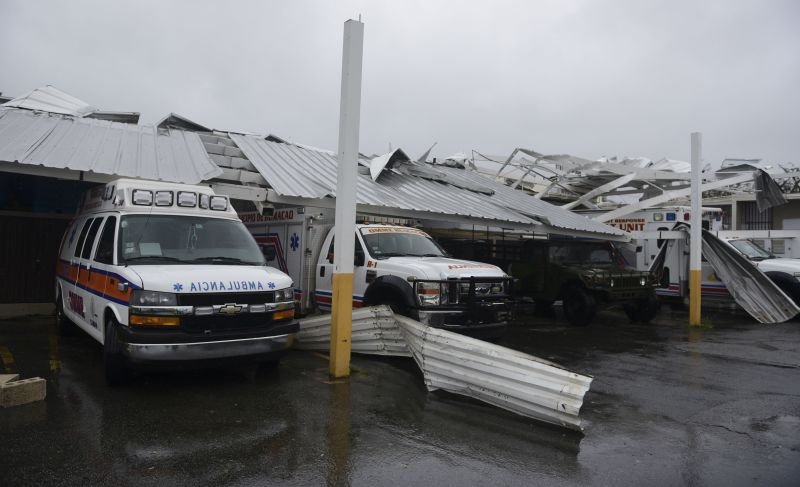 Rescue vehicles from the Emergency Management Agency stand trapped under an awning during the impact of Hurricane Maria