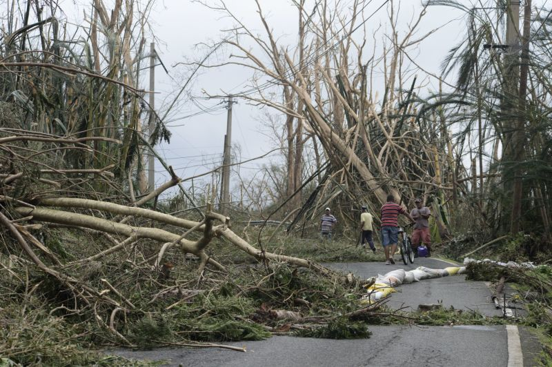 Locals help clear debris from a road after the passing of Hurricane Maria, in Yabucoa, Puerto Rico