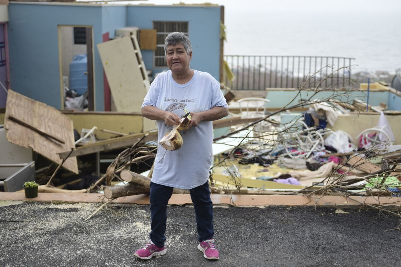 Rufina Fernandez standing in front of her daughters ruined house while eating a coconut a day after the impact of Hurricane Maria, in Yabucoa, Puerto Rico