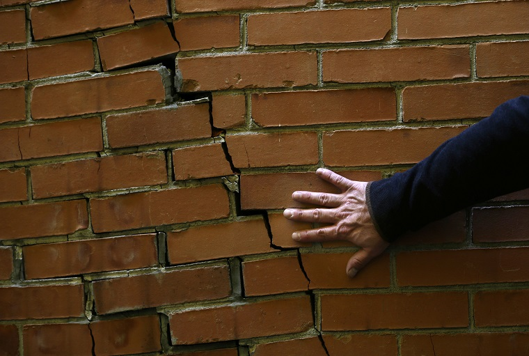 Architect Victor Marquez checks a cracked wall that was not caused by the recent earthquake during his survey of a seven-floor apartment building, in Mexico City's Roma neighborhood, Friday, Sept. 22, 2017. It is up to experts like architect Víctor Marquez, who thinks of himself as a building doctor, to bring peace of mind, or recommend aggressive treatment, to fearful apartment dwellers in the aftermath of Mexico's 7.1 magnitude quake that struck on Sept. 19. (AP Photo/Marco Ugarte)