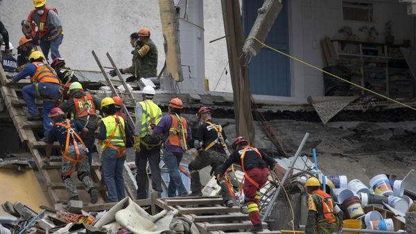 Rescue workers quickly evacuate the site of a felled office building brought down by a 7.1-magnitude earthquake, in the Roma Norte neighborhood of Mexico City, Sunday, Sept. 24, 2017. As rescue operations stretched into day 6, residents throughout the capital have held out hope that dozens still missing might be found alive. (AP Photo/Moises Castillo)
