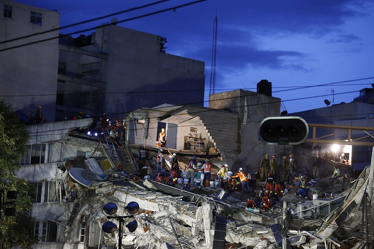 Rescuers race to save people believed to be still alive inside a collapsed office building in the Roma Norte neighborhood of Mexico City, as night falls Friday, Sept. 22, 2017, three days after a 7.1 magnitude earthquake. Hope mixed with fear Friday in Mexico City, where families huddled under tarps and donated blankets, awaiting word of their loved ones trapped in rubble. (AP Photo/Rebecca Blackwell)