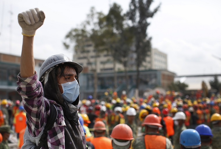 A young volunteer raises his fist as a sign to keep silent as dogs search through the rubble of a 7.1 quake-collapsed four-story clothing factory, in Mexico City, Friday, Sept. 22, 2017. Rescue operations stretched into a fourth day Friday, spurring hope among desperate relatives gathered at the sites of buildings collapsed by Tuesday's powerful earthquake. (AP Photo/Dario Lopez-Mills)