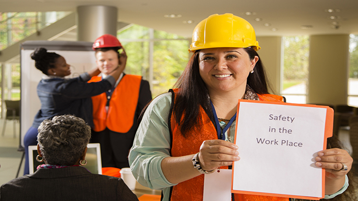 Woman in hard hat holding sign safety training with coworkers