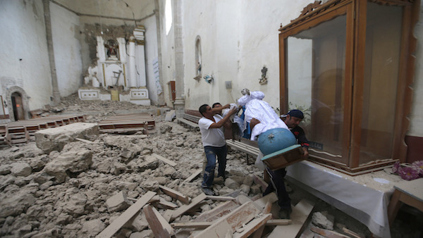 Workers rescue a religious statue from the heavily damaged former convent of San Juan Bautista, in Tlayacapan, Morelos state, Mexico. (Source: AP Images)