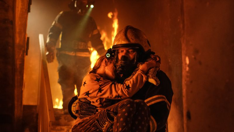 fireman rescuing child from burning home