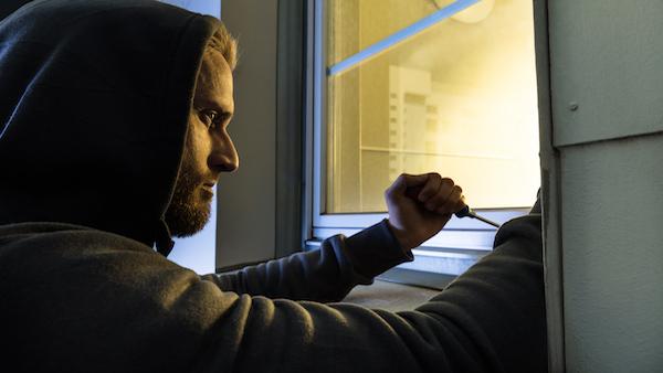 Burglar opening a window
