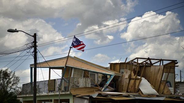 A political party banner waves over a home damaged in the passing of Hurricane Maria, in the community of Ingenio in Toa Baja, Puerto Rico, Monday, Oct. 2, 2017. (AP Photo/Ramon Espinosa)