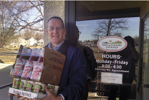 Loren Brabec delivers food items Mora office collected for local food shelf