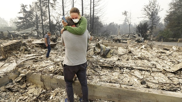 Todd Caughey hugs his daughter, Ella, on Oct. 10, 2017, as they visit the site of their home, which was destroyed by fires in Kenwood, Calif. (AP Photo/Jeff Chiu, File)