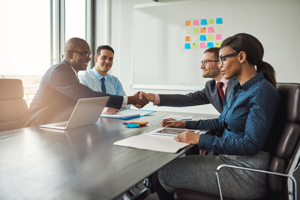 Two diverse business teams reach agreement