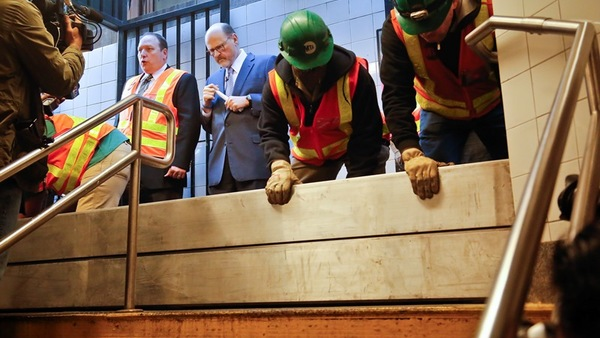 Metropolitan Transit Authority (MTA) workers demonstrate placing flood-prevention barriers to block a subway entrance, during a media tour of transit facilities with post Superstorm Sandy flood resiliency upgrades hosted by MTA Chairman Joseph Lhota, center, and MTA Sandy Program Manager Robert Laga, second from left, Oct. 27, 2017, in New York. (AP Photo/Bebeto Matthews)