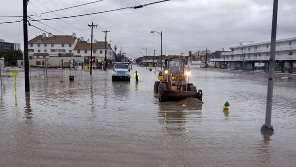 Crews work in flooded streets Tuesday, Oct. 30, 2012, in Ocean City, N.J., as they try to open drains and push the sand back toward the beach after the storm surge from Sandy flooded much of the town. er to more than 6 million homes and businesses.