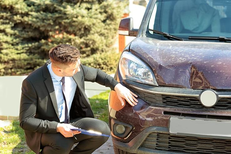 Adjuster reviews damage to auto