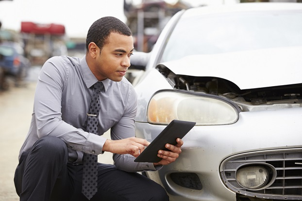 Young insurance adjuster using a tablet