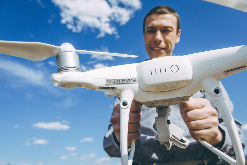 man holding a drone and showing the registration number