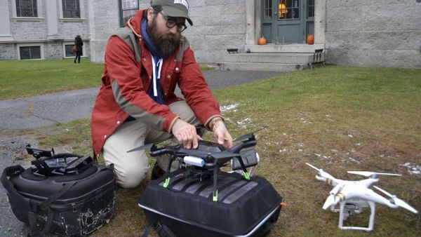 In this Nov. 14, 2017, photo, Dartmouth's Chad Hill readies a drone to be flown over a site of a Shaker Village in Enfield, NH. Hill and his Dartmouth colleague Jesse Casana are using drones equipped with thermal imaging cameras to study a half-dozen archaeological sites around the world. (AP Photo/Michael Casey)