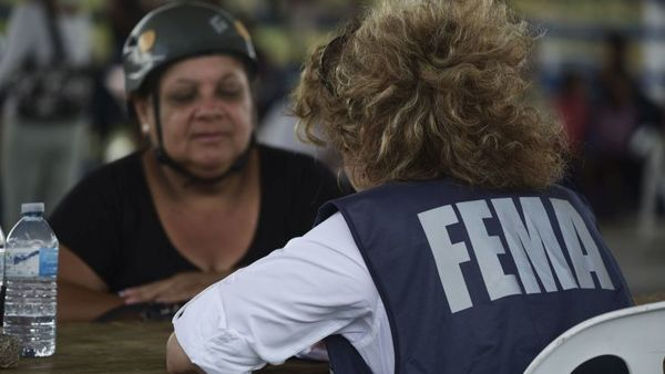 A resident meets with a FEMA representative to file forms for federal aid in the aftermath of Hurricane Maria at the Jose de Diego Elementary School in Las Piedras, Puerto Rico, Monday, Oct. 2, 2017. (AP Photo/Carlos Giusti)