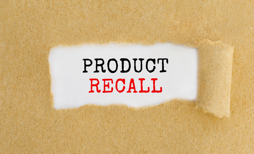 The words product recall emerging from a torn brown paper bag