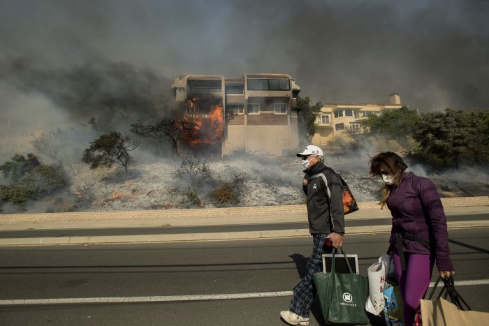 James and Josie Ralstin carry belongings from their Ventura, Calif., home as flames from a wildfire consume another residence