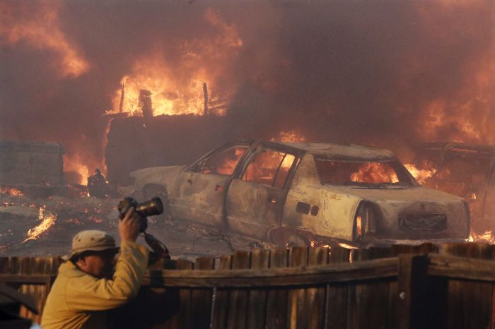 A news photographer takes pictures of a wildfire in the Lake View Terrace area of Los Angeles