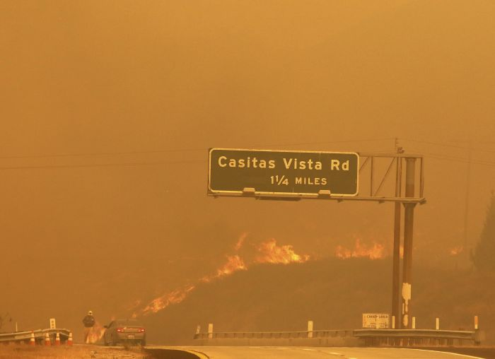 Flames and smoke shroud State Route 33 as a wildfire burns in Ventura, Calif.