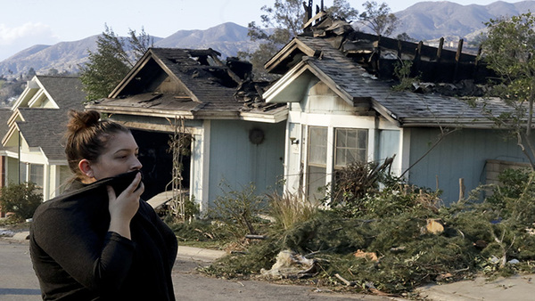Crystal Shore looks over the wildfire damaged neighbors home along Via San Anselmo in the Sylmar area of Los Angeles on Dec. 6, 2017. (AP Photo/Chris Carlson)