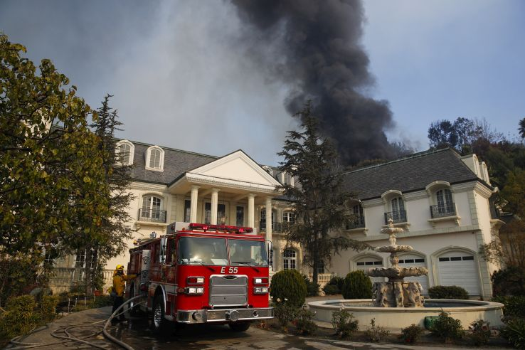 A fire truck is parked outside a mansion as smoke from a wildfire rises behind the property
