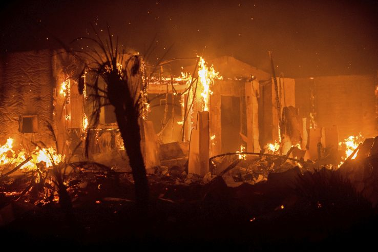 Flames consume a structure as the Lilac fire burns in Bonsall, Calif., on Friday, Dec. 8, 2017