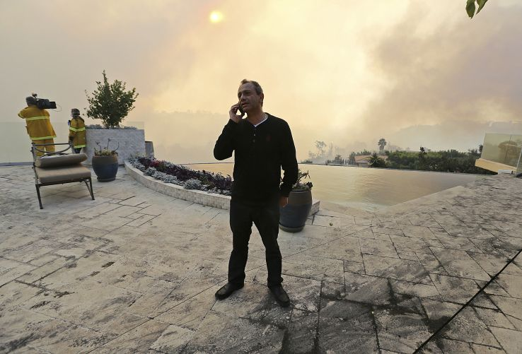 Maurice Kaboud makes a phone call after a wildfire threatened his home in the Bel Air district of Los Angeles