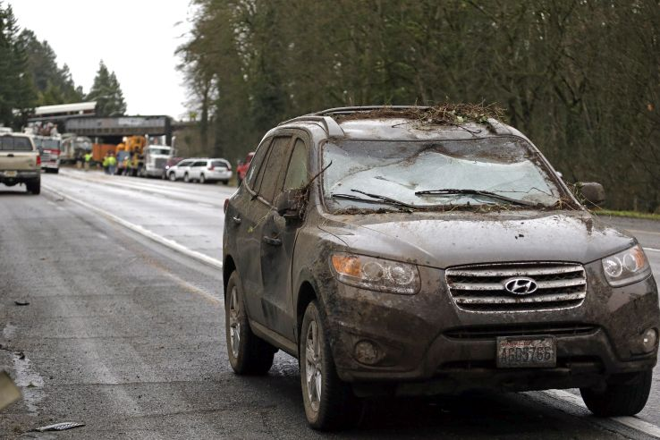 A car covered in mud and debris and with a smashed windshield and other damage sits parked on the shoulder just beyond where an Amtrak train lay spilled onto Interstate 5