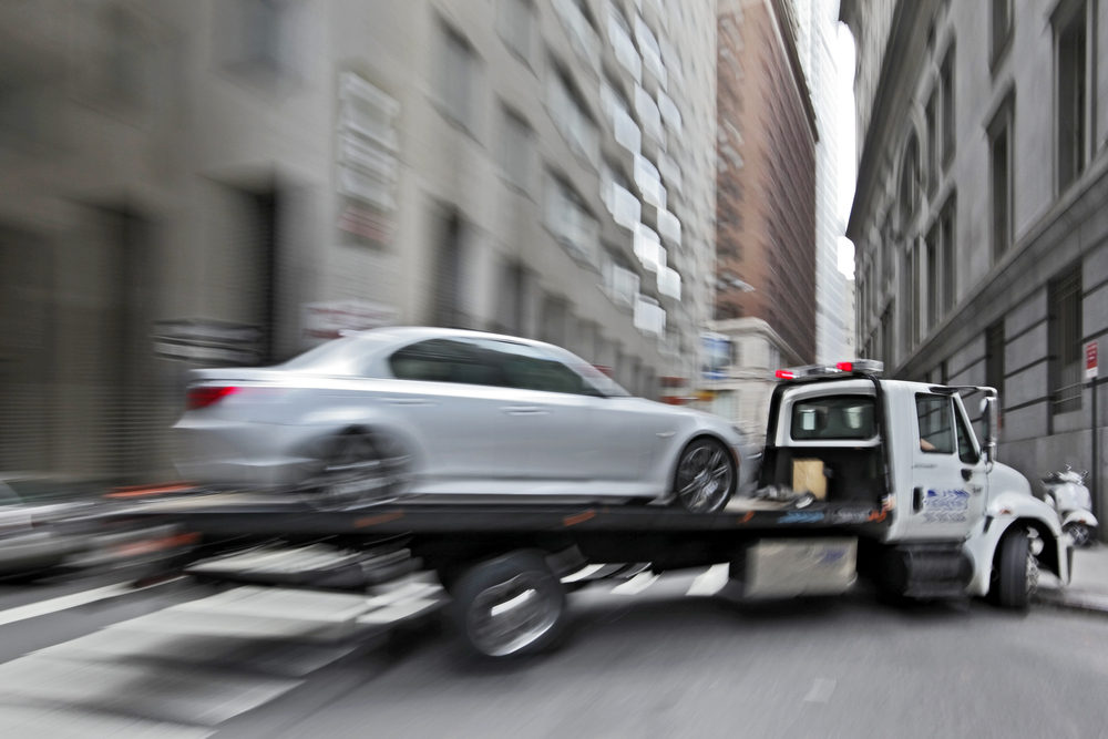 flatbed tow truck towing a car
